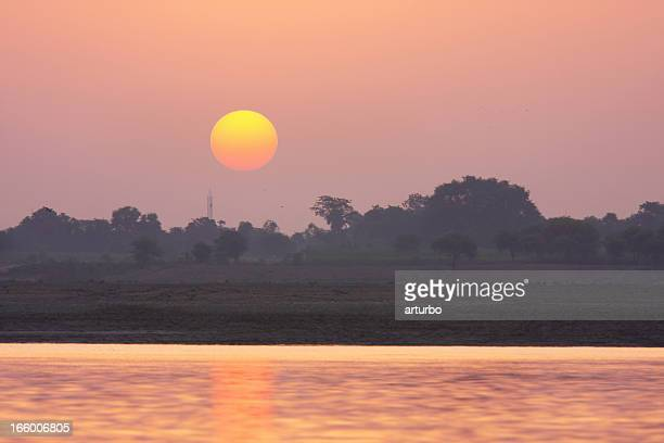 orange and red sunset over river in India