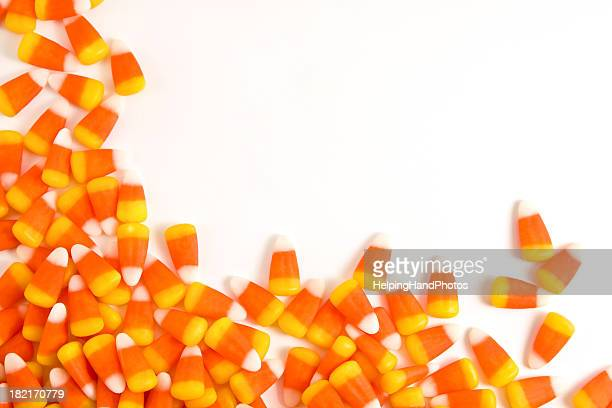 orange and yellow candy corn set against a white background - candy corn stock photos and pictures