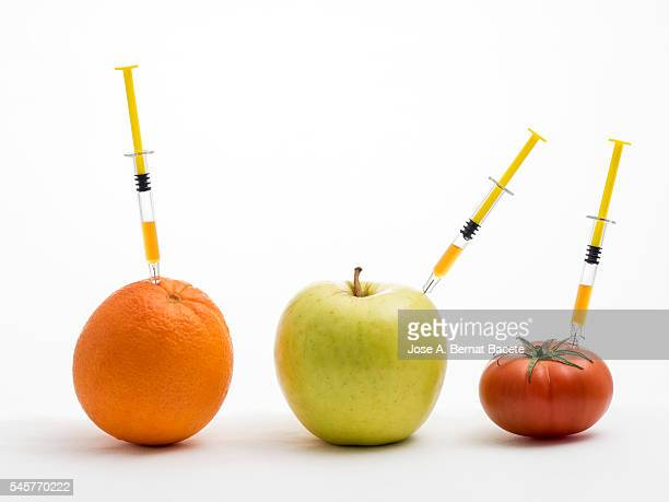 Orange, apple and tomato with a syringe stuck concept of transgenic foods