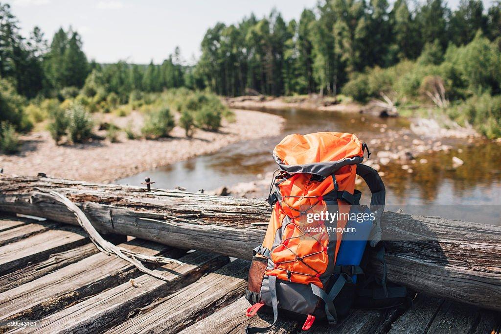 Orange backpack on wooden bridge in forest : Stock Photo