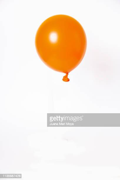 orange balloon, floating on white background - balloon stock pictures, royalty-free photos & images