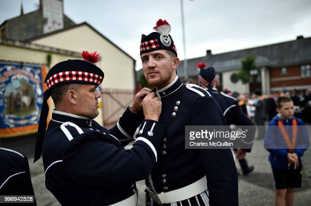 Orange band members prepare one another as they wait for the start of the annual 12th of July Orange march and demonstration takes place on July 12...