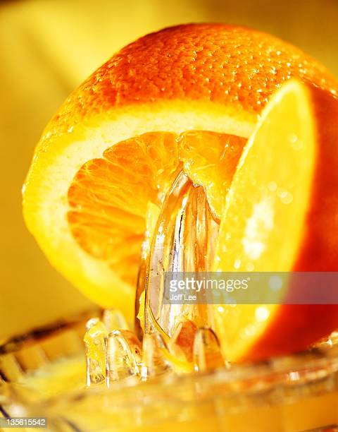 Orange being squeezed over glass juicer