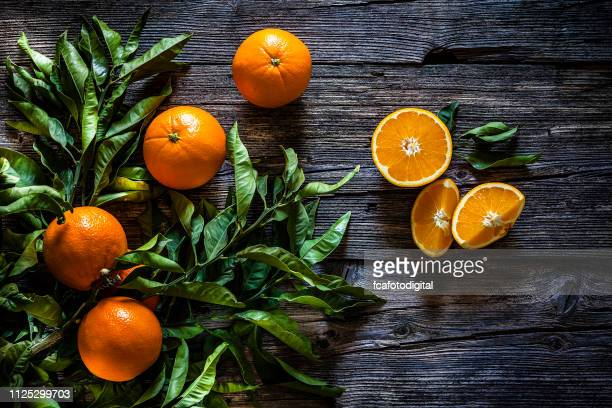 orange branch with orange fruits shot on rustic wooden table - arancione foto e immagini stock