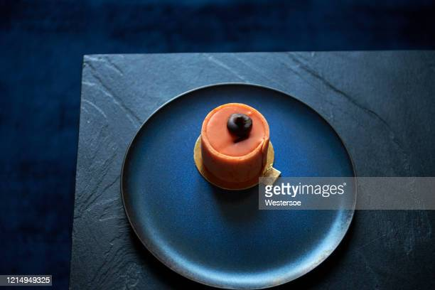 orange cake on blue plate - navy blue stock pictures, royalty-free photos & images