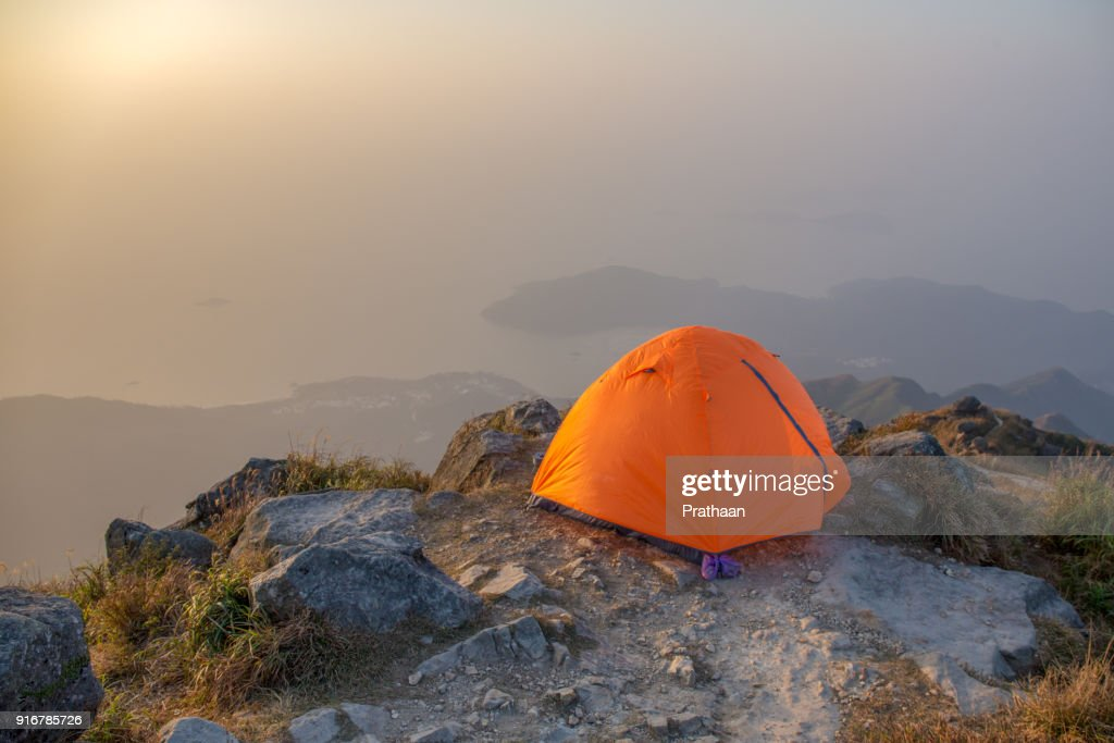 orange camping tent near cliff isolated on lantau peak, Hong Kong in sunrise and fog with copy space : Stock Photo