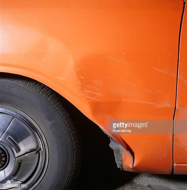 Orange car, close-up of damaged body panel and wheel