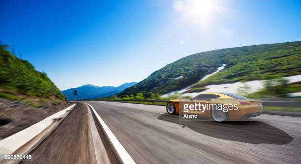 orange car driving on a mountain road - smart car stock photos and pictures