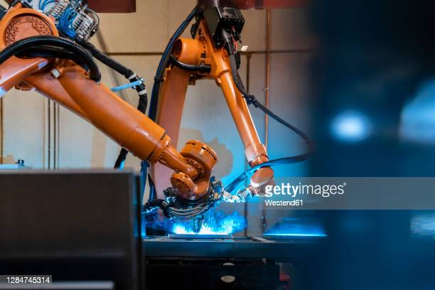 orange color robotic arms manufacturing in industrial factory - making stock pictures, royalty-free photos & images