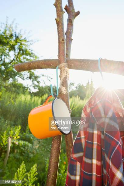 orange colored enamel cup and red checkered shirt hanging at wooden post in the garden, outdoor camping equipment - enamel stock pictures, royalty-free photos & images