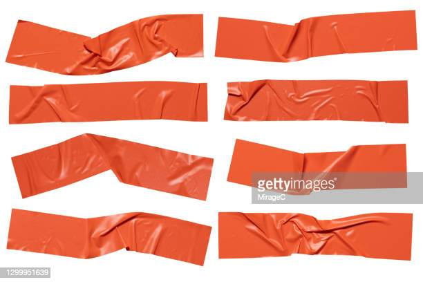 orange colored plastic adhesive tape stripes - adhesive tape stock pictures, royalty-free photos & images