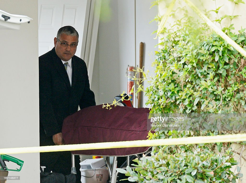 Orange County Coroner picks a body of a victim from a house on February 19, 2013 in Ladera Ranch, California. According to law enforcement officials six people were shot in cities of Tustin, Ladera Ranch and Orange, four of them fatally, including the suspected shooter, who apparently killed himself.