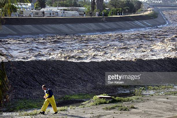 Orange County Fire Authority firefighter walks near area of San Juan Creek where storm waters tore chunks from the creek's concrete lining leaving...