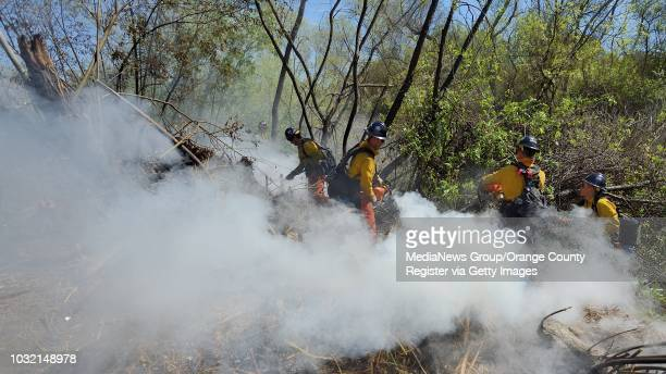Orange County Fire Authority firefighters clean up hot spots after a fire in Talbert Regional Park on Tuesday The fire started in a homeless...