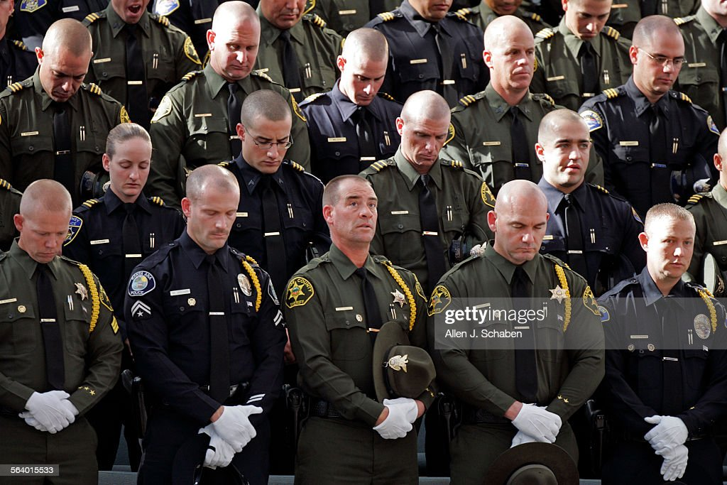 Orange county sheriff and police officers bow their heads in prayer orange county sheriff and police officers bow their heads in prayer during a memorial service for publicscrutiny Image collections