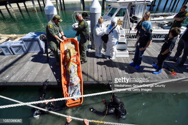 Orange County sheriff deputies remove a fake body from the water as members of the Thurston Middle School forensics class prepare to investigate in...