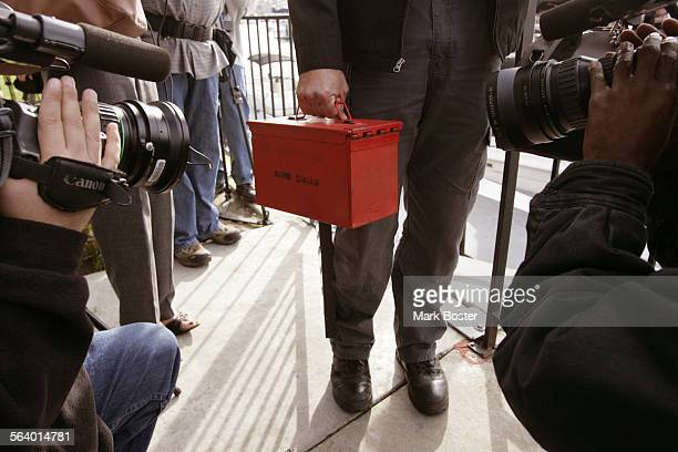 –Orange County Sheriff's Department Bomb Squad Investigator Steve Garrison holds a red ammo box containing the six blasting caps recovered in...