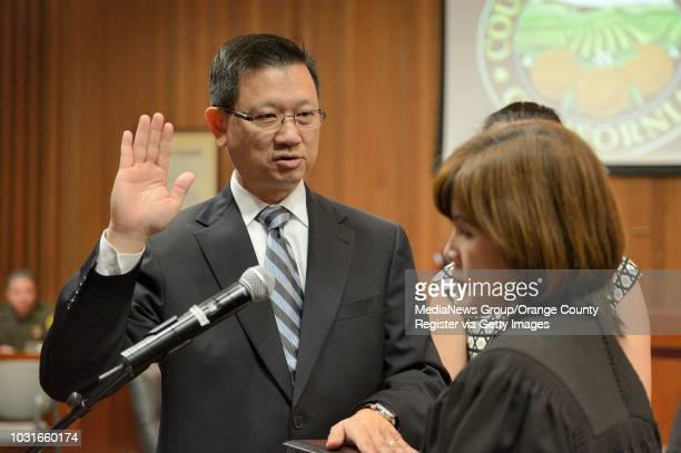 Orange County Supervisor Andrew Do takes the oath of office from his wife, Cheri Pham, as he stands with his daughters, Ilene Do, center, and...