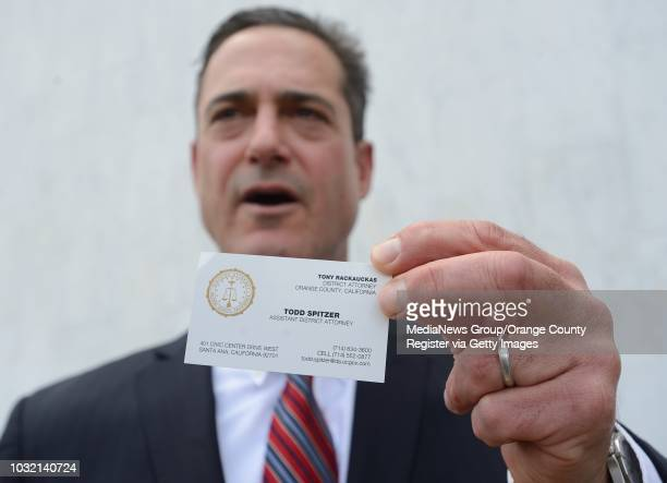Orange County Supervisor Todd Spitzer shows off a business card that says he is an assistant district attorney during an impromptu press conference...