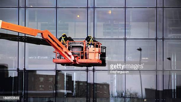 Orange crane on blue office building, installing windows