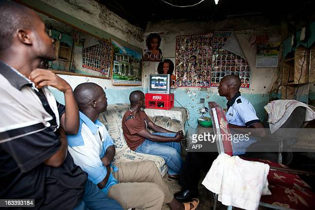Orange Democratic Movement supporters in the Bangladesh area of the Jomvu constituency in Mombasa watch TV in a barber shop on March 9 2013 after the...
