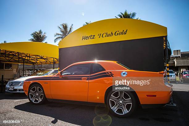 orange dodge challenger parked near hertz rental office - hertz stock pictures, royalty-free photos & images
