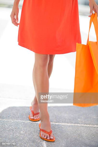 orange dressed woman with shopping bag and flip-flops - orange dress stock pictures, royalty-free photos & images