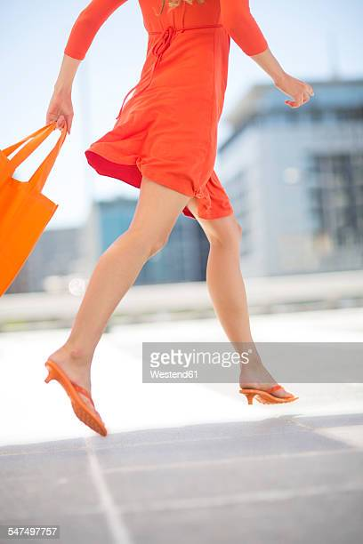 orange dressed woman with shopping bag - orange dress stock pictures, royalty-free photos & images