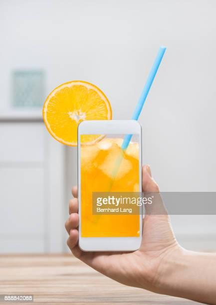 Orange Drink on phone screen, held by hand