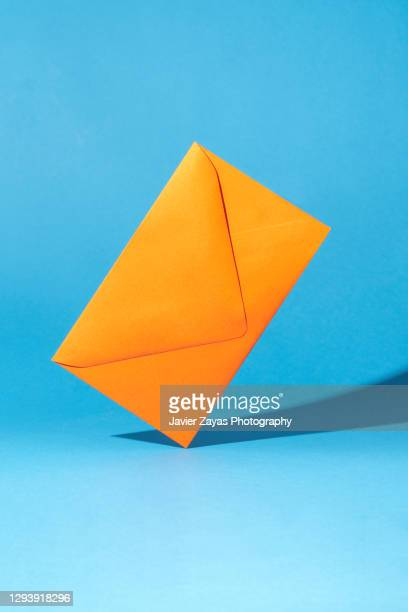 orange envelope on blue colored background - letter stock pictures, royalty-free photos & images