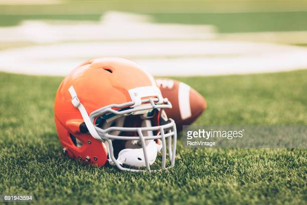 orange football helmet on field - american football strip stock pictures, royalty-free photos & images