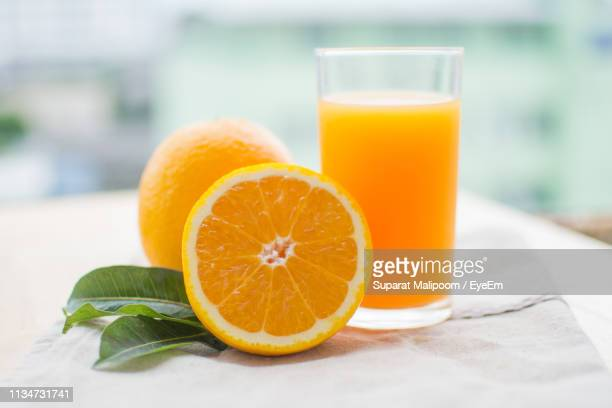 orange fruit and juice in glass on table - orange juice stock pictures, royalty-free photos & images