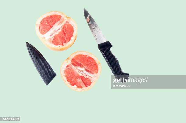 orange fruit cut in half by knife on pastel background