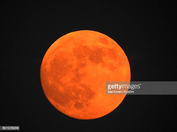 Orange Full Moon Against Clear Sky At Night