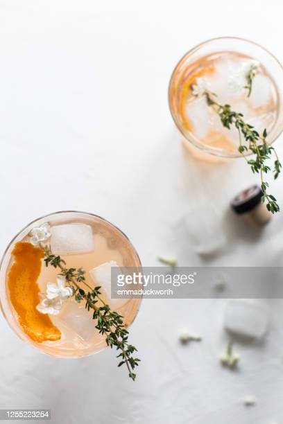 orange gin cocktail with thyme - cocktail stock pictures, royalty-free photos & images