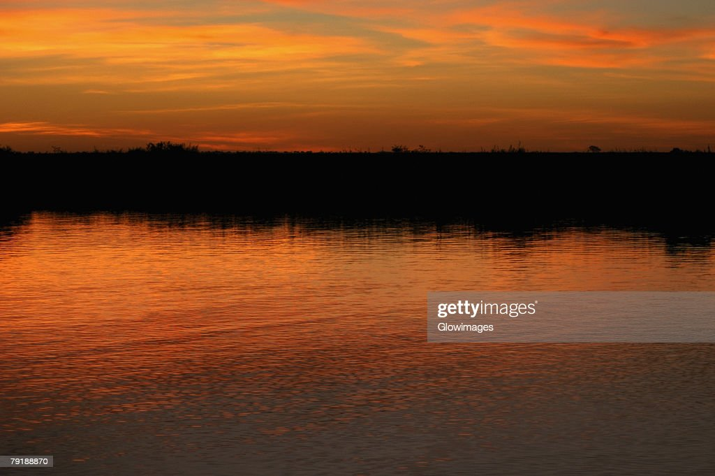 Orange glow of the sky in water at sunset, Okavango Delta, Botswana : Stock Photo