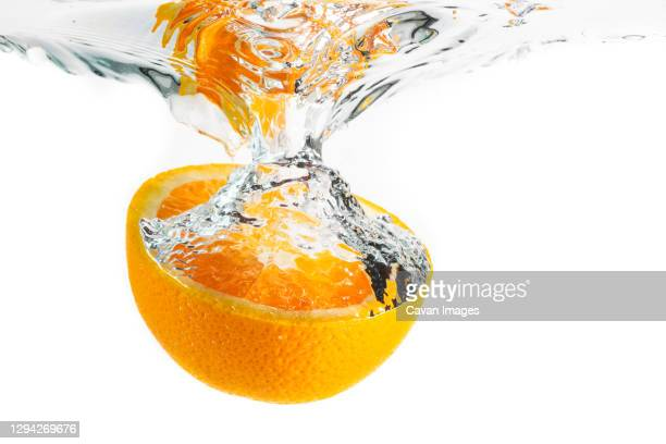 orange half splashing into water and sinking isolated on white background. citrus drink concept. - juteux photos et images de collection
