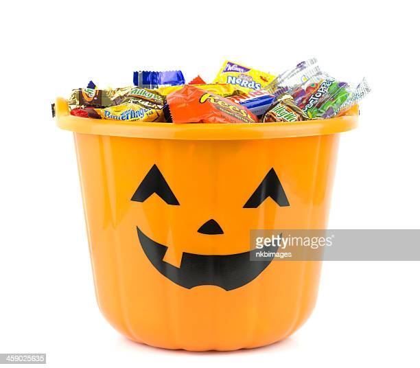 orange halloween bucket filled with candy - bucket stock pictures, royalty-free photos & images