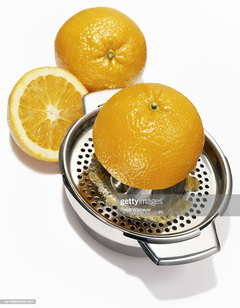 Orange halves and metal juicer, studio shot, close-up : Foto stock