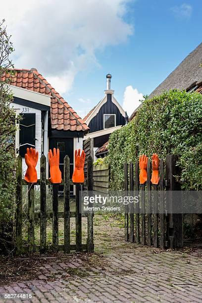 Orange handgloves on garden fence