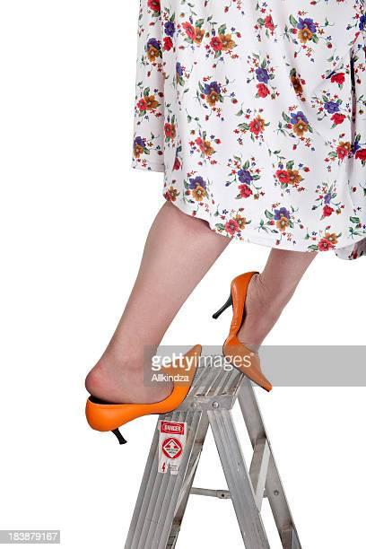 orange heeled woman slips off ladder - nylon feet stockfoto's en -beelden