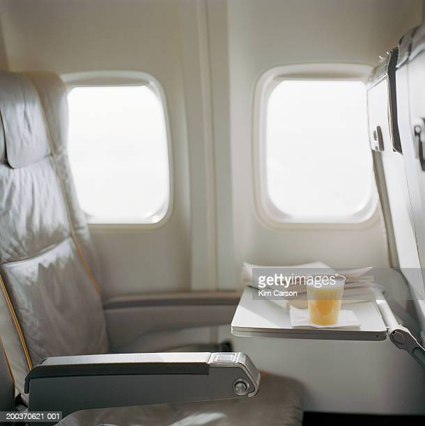 Orange juice and book on open airplane tray, side view