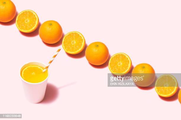 le jus d'orange plat s'est couché sur le fond rose - part of a series photos et images de collection