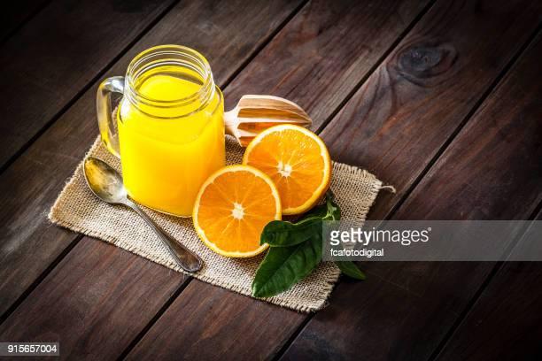 Pot de verre de jus d'orange tourné sur une table en bois rustique