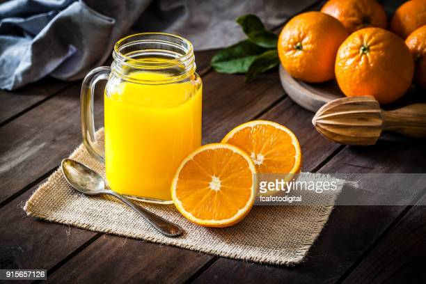 orange juice glass jar shot on rustic wooden table - orange imagens e fotografias de stock