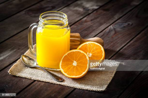 Orange juice glass jar shot on rustic wooden table
