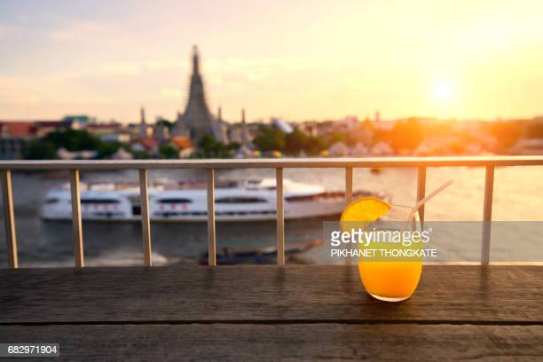 Orange juice on the bar with Wat Arun Temple at sunset in bangkok Thailand