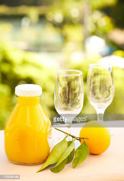 Jugo de naranja, que se sirve por la mañana temprano, contra un fondo de naturaleza
