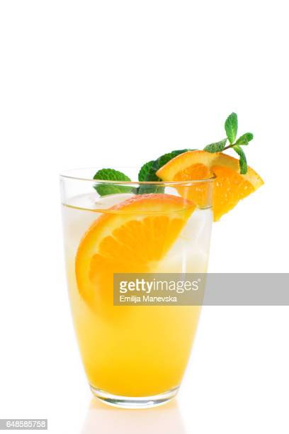 Orange juice with fresh mint leaf on white background