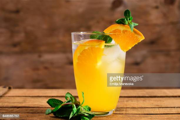 Orange juice with fresh mint leaf on wooden background